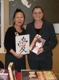 "Teresa LeYung Ryan shows Chinese word for ""love"" and Barbara Whittaker holds Teresa's novel Love Made of Heart"